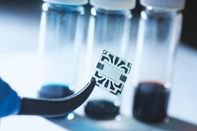 A new flexible graphene solar cell developed at MIT is seen in the transparent region at the center of this sample. Around its edges are metal contacts on which probes can be attached during tests of device performance.