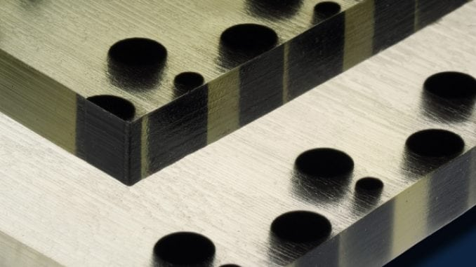 Polymer material produced by a 3-D printer includes soft, flexible material (clear or lighter tone) with particles of hard material (black) embedded, in predetermined arrangements. When the material is compressed, its surface become bumpy in a pattern determined by the hard particles.